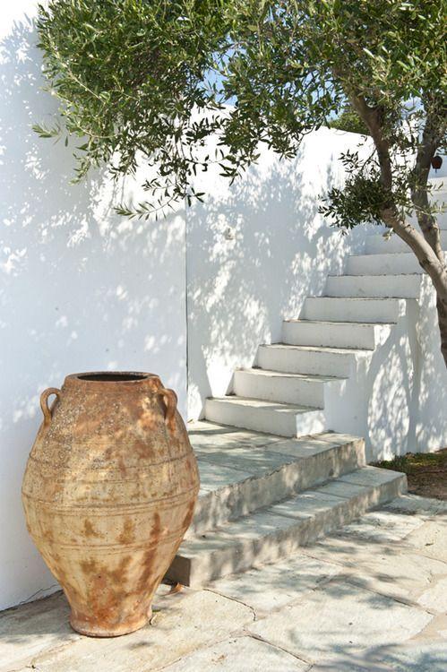 Très grand pot à arbuste qui sert de décoration de bas d'escalier