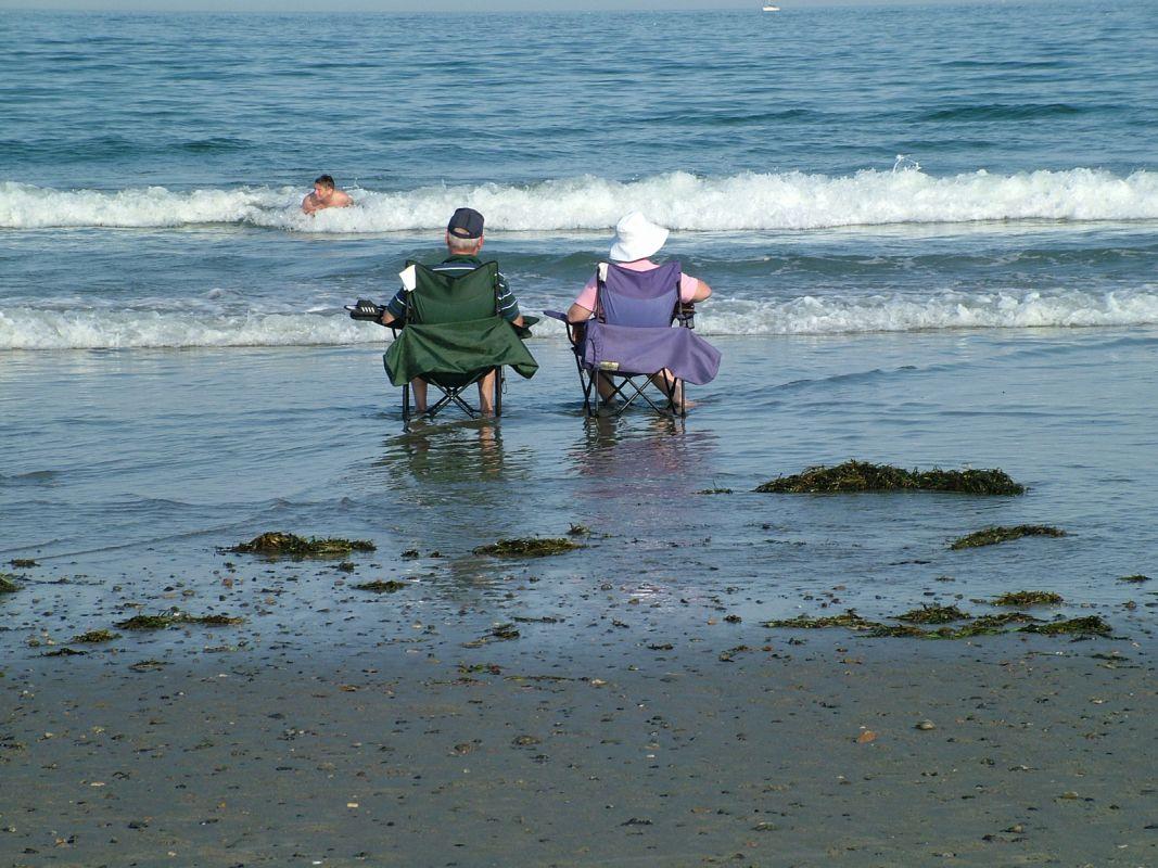 Couple assis sur le bord de la mer