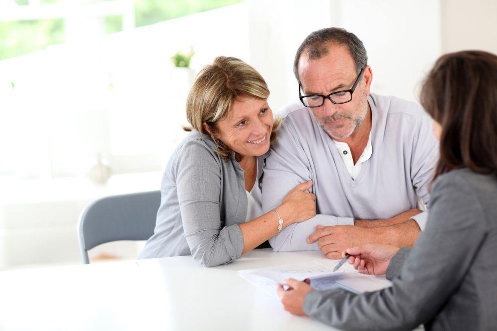 Couple se faisant expliquer les détail d'un contrat de courtage par un courtier immobilier