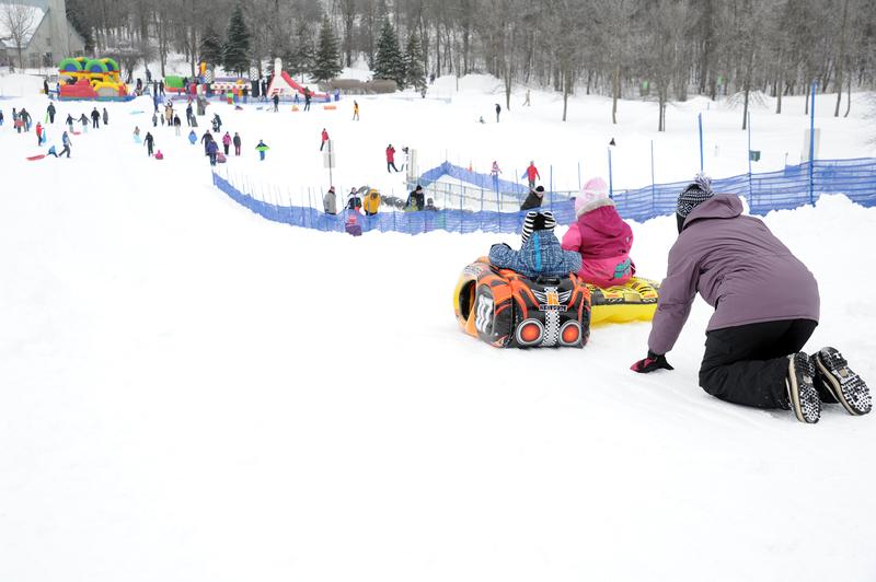 Famille sur une pente de ski avec tobogan à Longueuil.