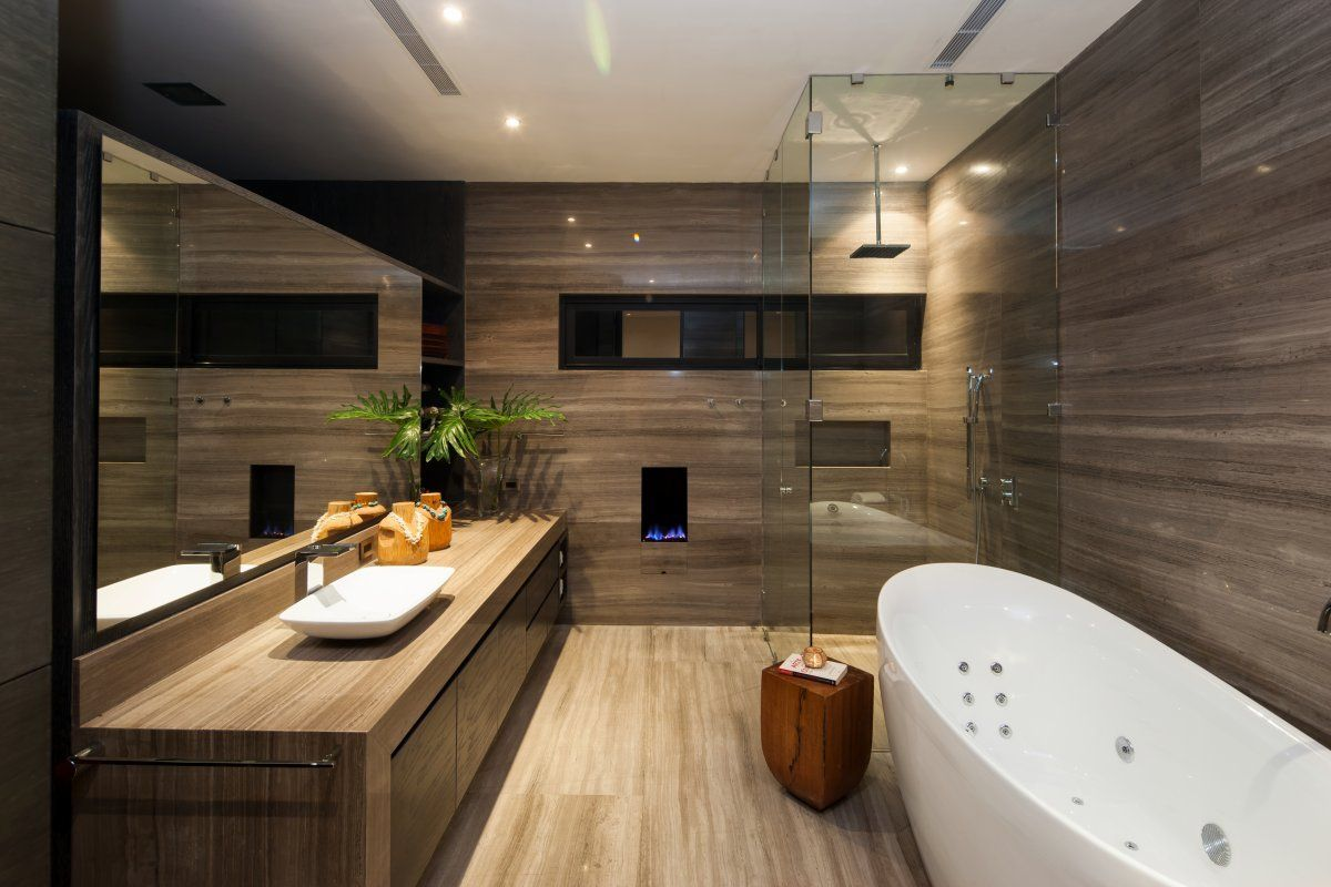 Salle de bain avec mur en marbre et douche vitrée.