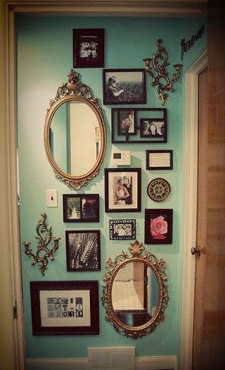 Mur décoratif style vintage avec mirroirs, cadres et ornements.