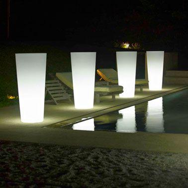 Énorme pots à fleurs rétro-éclairé sur le bord de la piscine