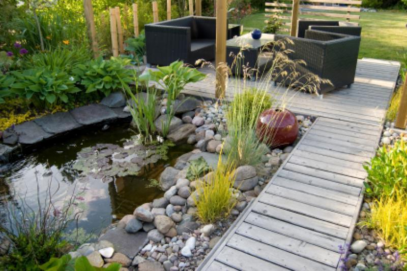 Aménagement décoratif de terrasse extérieur avec bois exotique avec petit étang naturelle