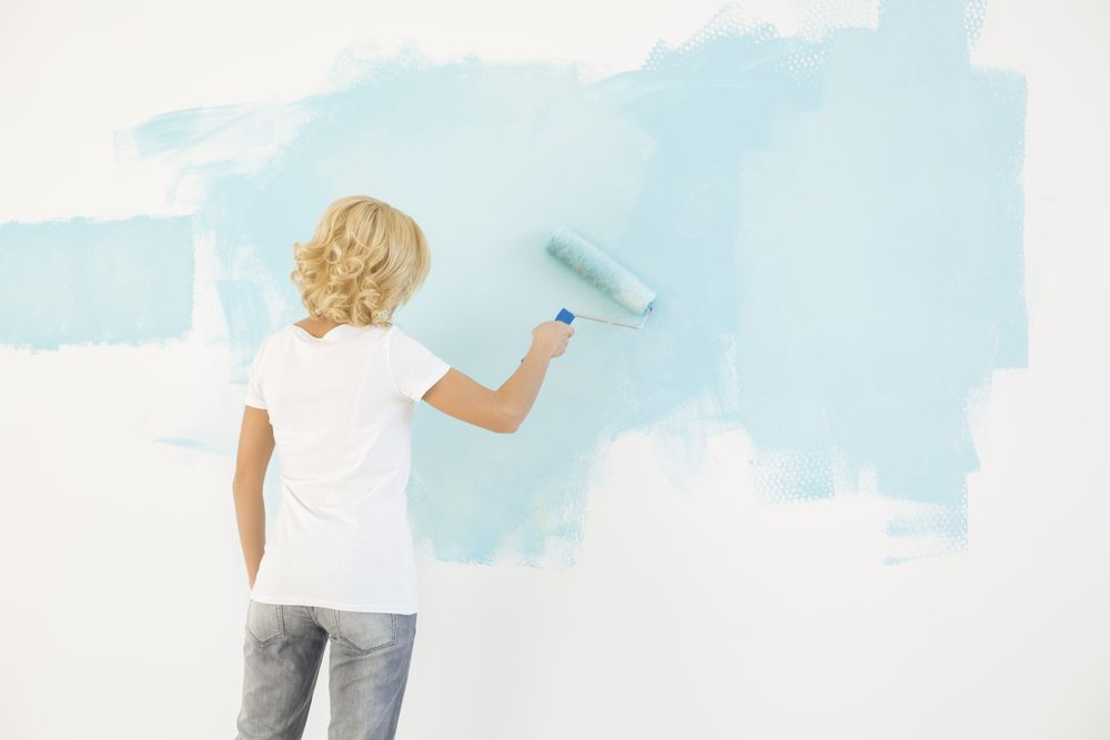 Dame en train de peinturer un mur couleur bleu pâle