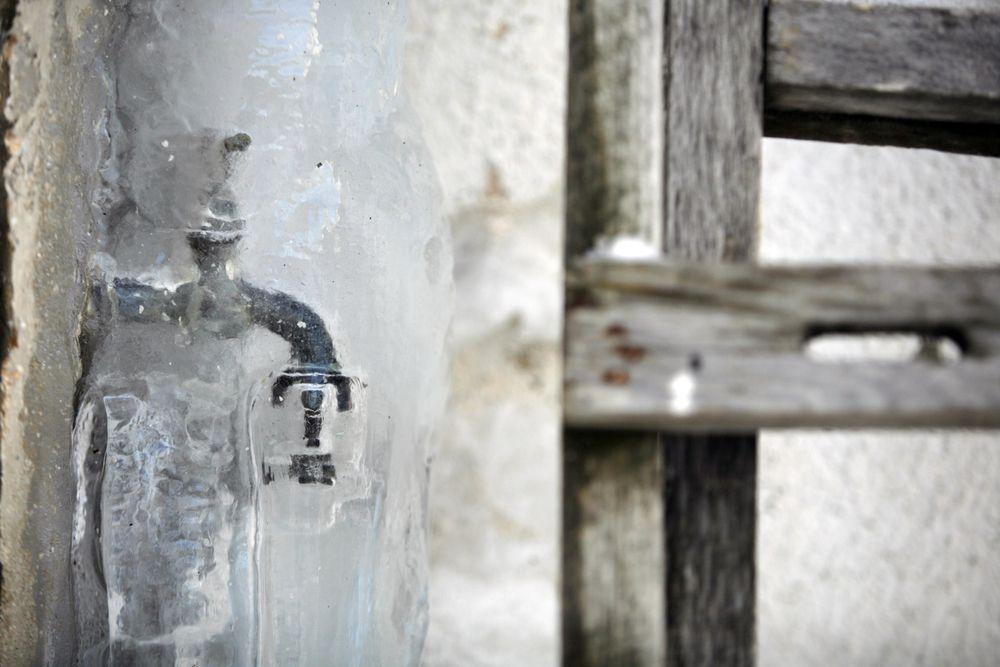 Robinet et boyau d'arrosage pris dans la glace l'hiver