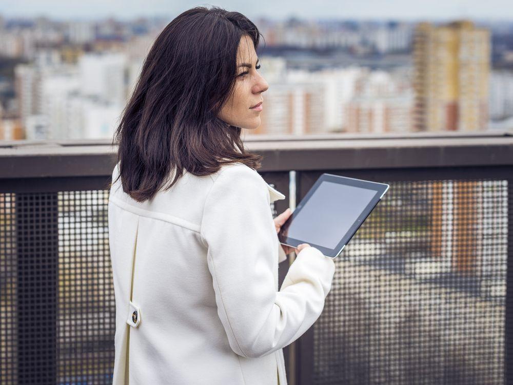Courtier immobilier qui attend son client avec son iPad pour montrer des comparatifs