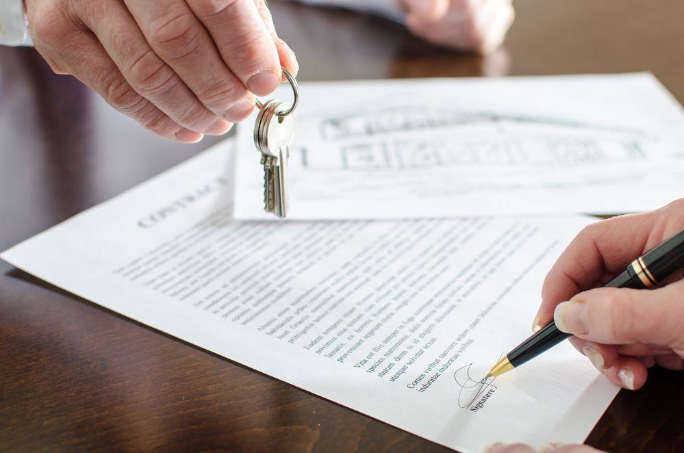 Remise des clefs d'une propriété, symbole de l'assistance du courtier immobilier jusqu'à la signature des documets chez le notaire