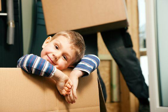 Petit garçon espiègle se cachant dans une boite bien heureux de démnager