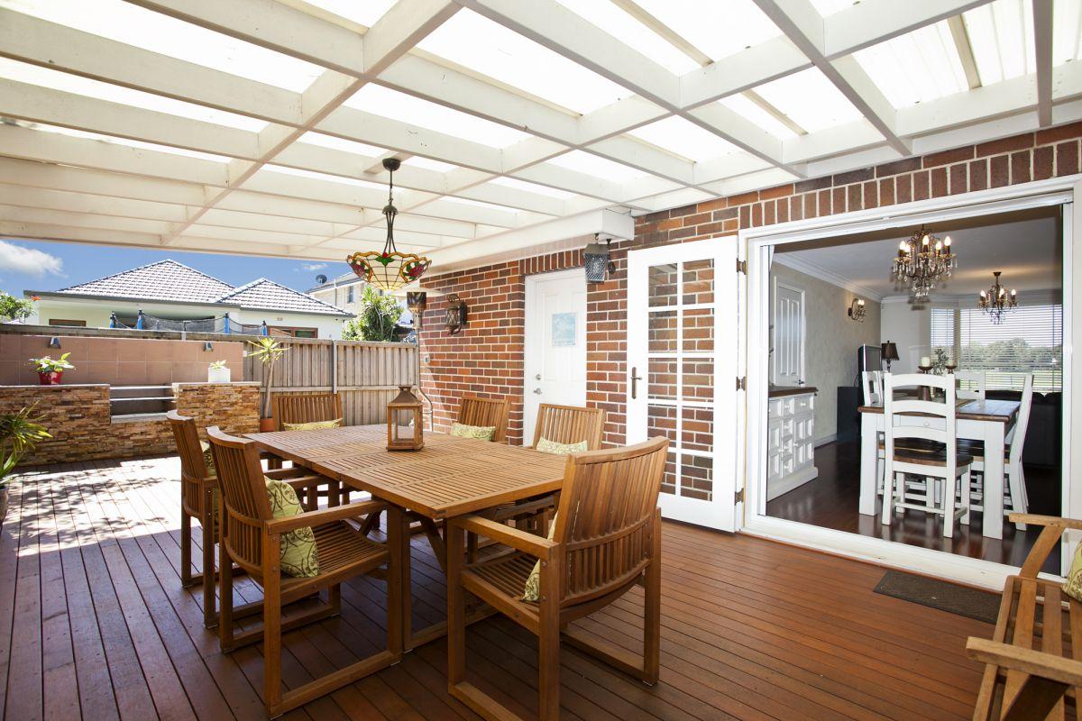 Grande terrasse attenante à la salle à manger en bois avec toit style pergolas