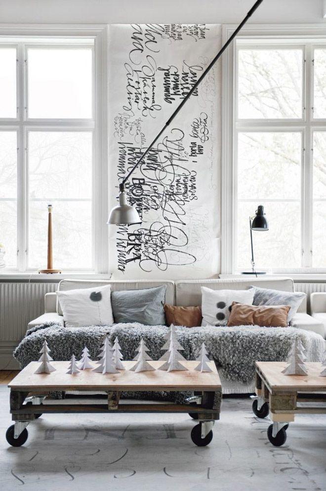 Salon style scandinave avec mur décoré avec un imprimé d'écriture à la main noir sur blanc