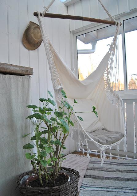 Porche de maison de campagne avec hamac blanc suspendu